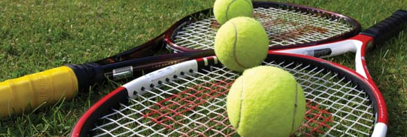 Two tennis racquets on some grass with balls on